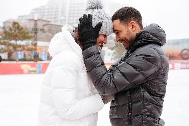Coppie amorose felici che pattinano alla pista di pattinaggio sul ghiaccio all'aperto. Foto Gratuite
