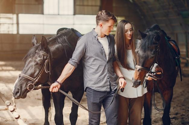 Coppie amorose sveglie con il cavallo sul ranch Foto Gratuite