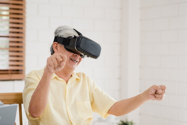 Coppie anziane asiatiche facendo uso del simulatore di realtà virtuale e della compressa che gioca nel salone Foto Gratuite