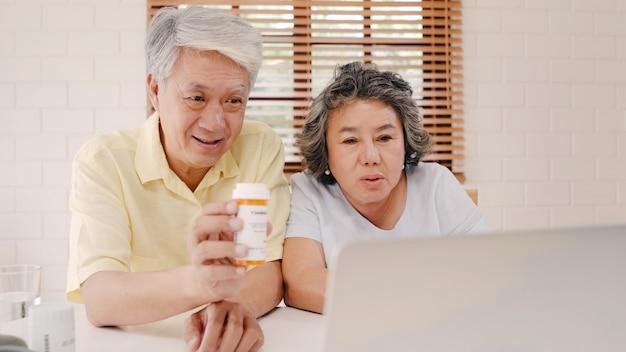 Coppie anziane asiatiche facendo uso della conferenza del computer portatile con medico circa informazioni della medicina in salone, coppia facendo uso del tempo insieme mentre trovandosi sul sofà a casa. Foto Gratuite