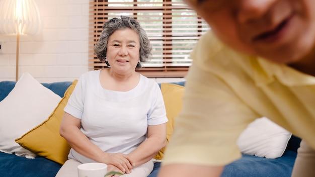 Coppie anziane asiatiche facendo uso della video conferenza dello smartphone con il nipote mentre trovandosi sul sofà in salone a casa. Foto Gratuite