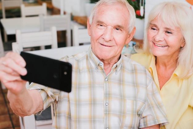 Coppie anziane che prendono selfie che sorride a casa Foto Gratuite