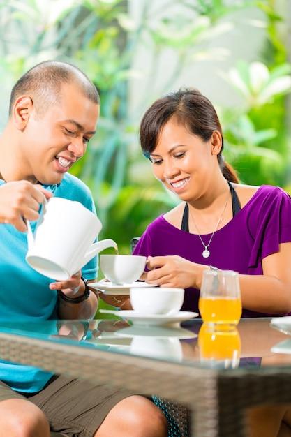 Coppie asiatiche che mangiano caffè sul portico domestico Foto Premium
