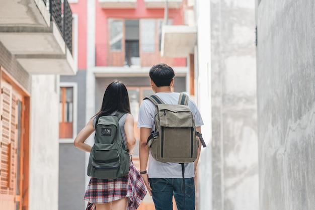 Coppie asiatiche del viaggiatore con zaino e sacco a pelo del viaggiatore che ritengono viaggio felice a pechino, cina, coppie allegre del giovane adolescente che camminano a chinatown. Foto Gratuite