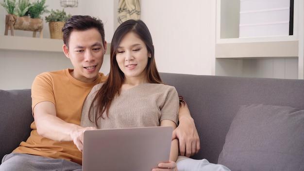 Coppie asiatiche facendo uso del computer portatile per il web di ricerca in salone a casa Foto Gratuite