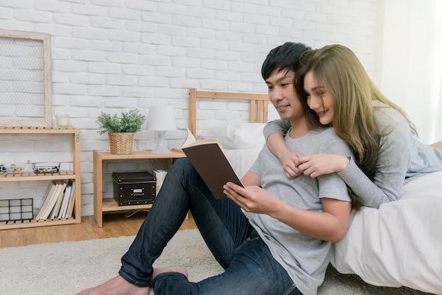 Coppie asiatiche felici che leggono il libro o il taccuino sul letto Foto Premium