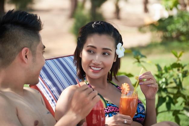 Coppie asiatiche felici che si siedono nei lettini del sole all'aperto alla località di soggiorno e che bevono succo fresco Foto Gratuite