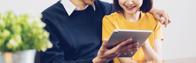 Coppie asiatiche felici facendo uso della compressa digitale e online insieme a casa Foto Premium