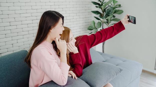 Coppie asiatiche lesbiche che utilizzano selfie dello smartphone in salone a casa Foto Gratuite