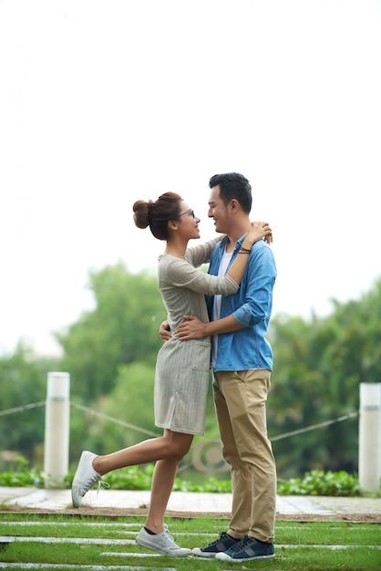 Coppie asiatiche spensierate che abbracciano alla data Foto Gratuite