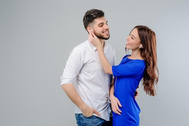 Coppie attraenti che ascoltano la musica che condivide i tappi per le orecchie Foto Premium