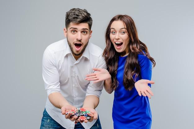 Coppie attraenti che giocano online in casinò con i chip di mazza isolati sopra fondo grigio Foto Premium