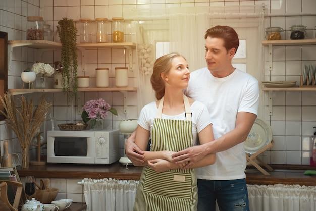 Coppie caucasiche romantiche nell'amore che si diverte insieme nel fronte di kitchen.iling. Foto Premium