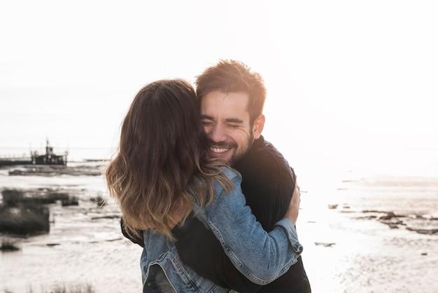 Coppie che abbracciano sulla riva del mare Foto Gratuite