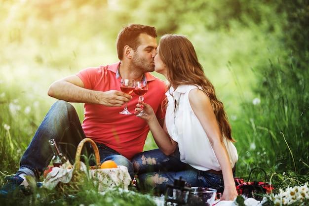Coppie che baciano e tenendo bicchieri di vino Foto Gratuite