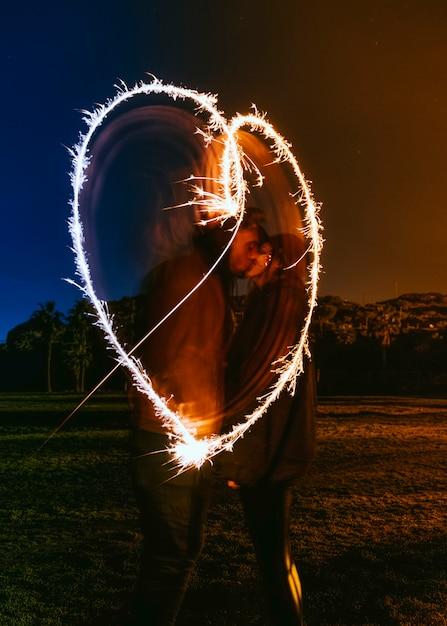 Coppie che baciano vicino al cuore di disegno da stelle filanti in strada buia Foto Gratuite