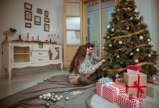 Coppie che decorano l'albero di natale che si siede sul pavimento Foto Gratuite