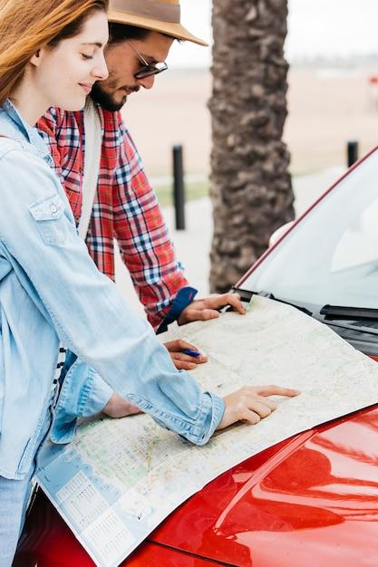 Coppie che esaminano il programma di strada sull'automobile rossa Foto Gratuite