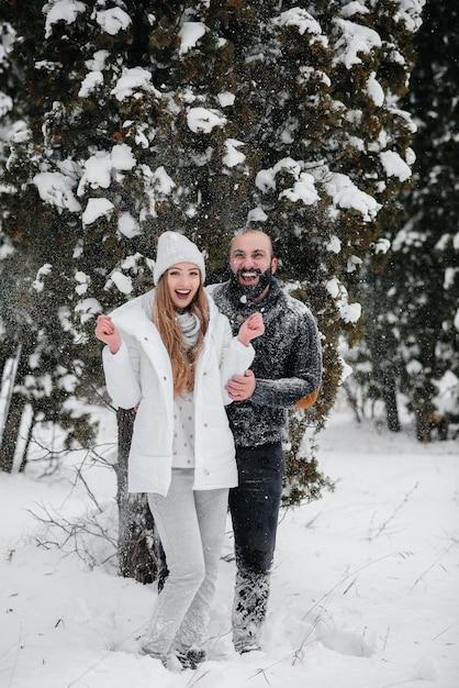Coppie che giocano con la neve nella foresta Foto Premium