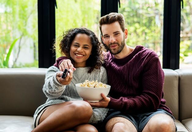 Coppie che guardano tv che ha popcoprn Foto Premium