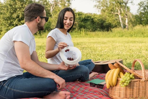Coppie che mangiano le ciliege su una coperta da picnic Foto Gratuite