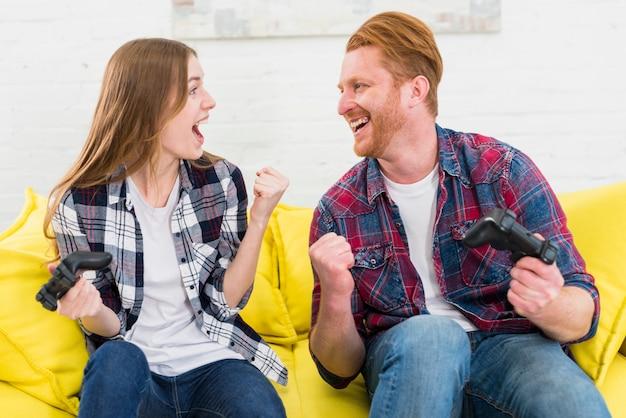 Coppie che si guardano a vicenda stringendo il pugno dopo aver vinto il videogioco Foto Gratuite
