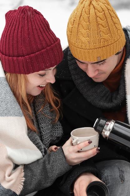 Coppie che si siedono e che bevono il primo piano delle bevande calde Foto Gratuite