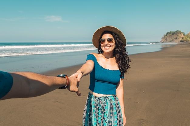 Coppie che si tengono per mano camminando sulla spiaggia Foto Gratuite
