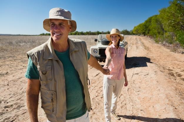 Coppie che si tengono per mano mentre camminando sul paesaggio Foto Gratuite