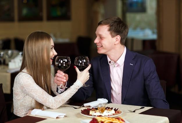 Coppie che tostano i bicchieri di vino in un ristorante di lusso. Foto Premium