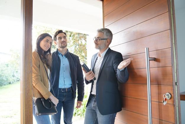 Coppie con l'agente immobiliare che visita casa moderna Foto Premium