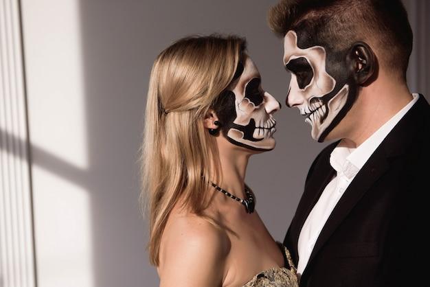 Coppie con trucco del cranio scuro su priorità bassa bianca. halloween Foto Premium