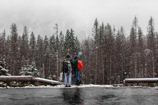 Coppie dei turisti con gli zainhi che stanno nella foresta nevosa di inverno e che considerano gli alberi. Foto Premium