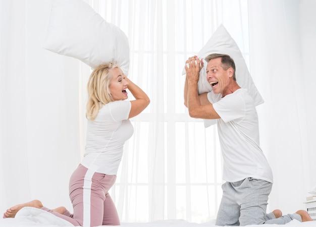 Coppie del colpo medio che hanno una lotta di cuscino Foto Gratuite