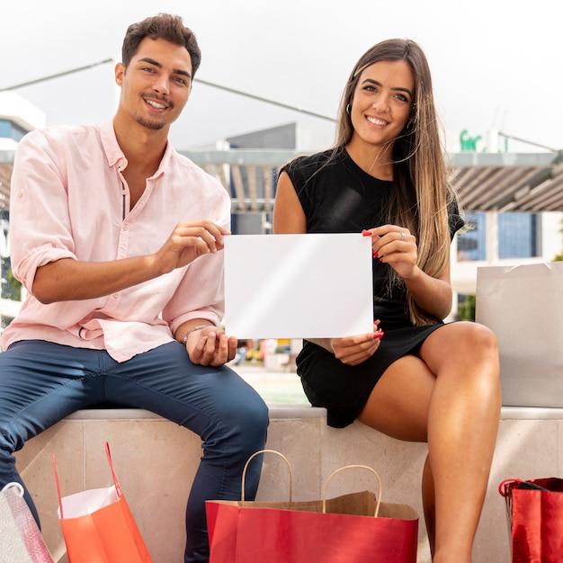 Coppie di acquisto che tengono il modello in bianco della carta Foto Gratuite