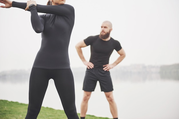 Coppie di forma fisica che allungano all'aperto nel parco vicino all'acqua. giovane uomo e donna barbuti che si esercitano insieme nella mattina Foto Gratuite