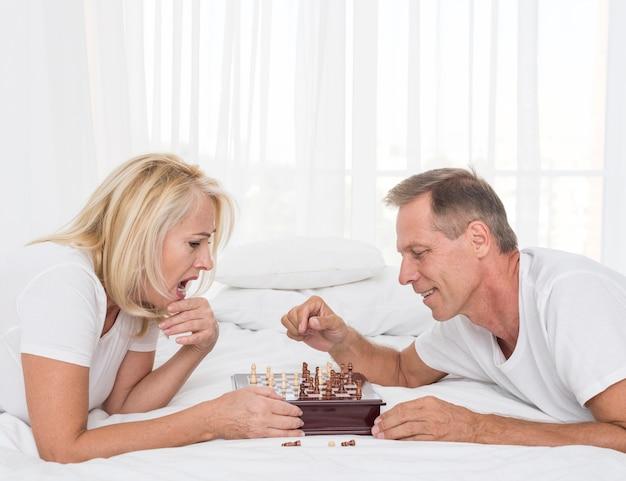 Coppie di vista laterale che giocano scacchi nella camera da letto Foto Gratuite