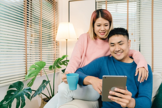 Coppie dolci asiatiche attraenti facendo uso della compressa mentre trovandosi sul sofà quando si rilassano nel loro salone Foto Gratuite