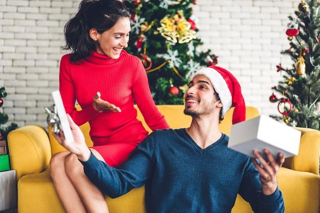 Coppie dolci romantiche in cappelli di santa divertendosi decorando l'albero di natale e sorridendo mentre celebrando la notte di san silvestro e godendo passare il tempo insieme uomo che dà sorpresa del contenitore di regalo alla donna Foto Premium