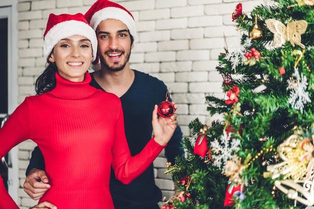 Coppie dolci romantiche in cappelli di santa divertendosi decorando l'albero di natale e sorridendo mentre celebrando la notte di san silvestro Foto Premium