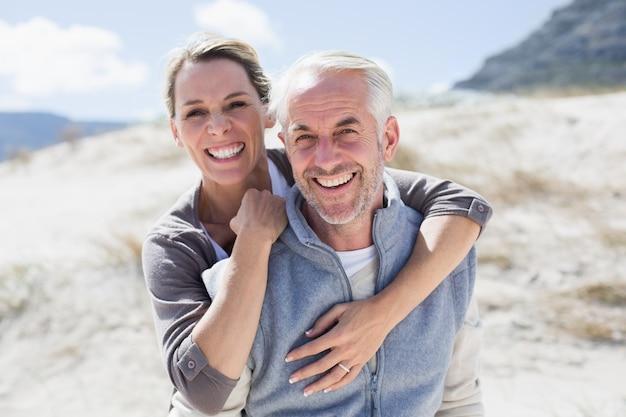 Coppie felici abbraccianti sulla spiaggia che guarda l'obbiettivo Foto Premium