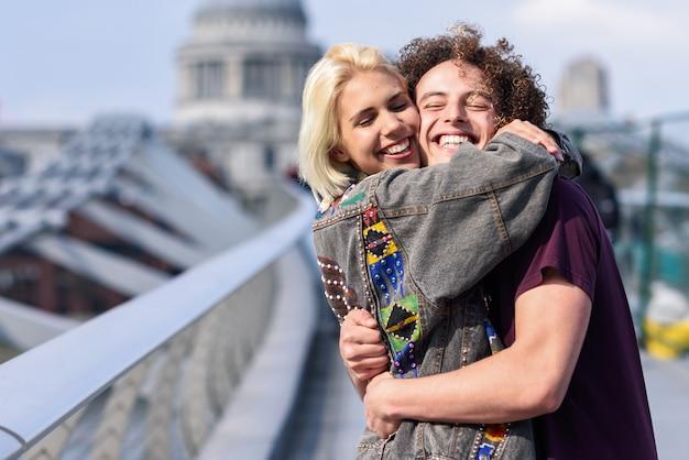 Coppie felici che abbracciano dal ponte del millennio, sul tamigi, a londra. Foto Premium