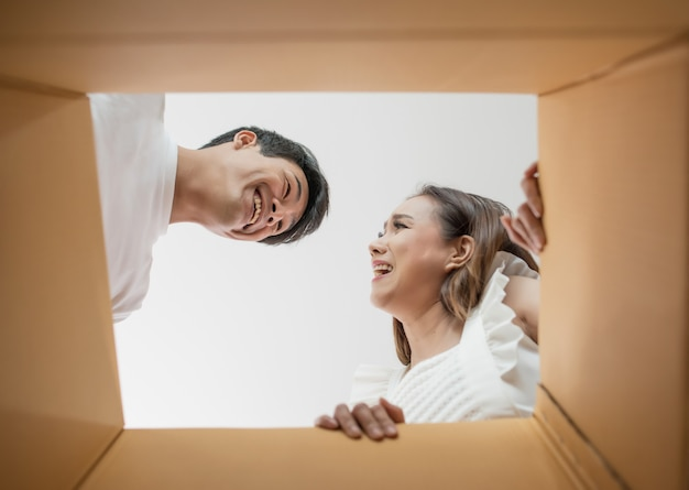Coppie felici che aprono una scatola e che guardano dentro al prodotto Foto Gratuite