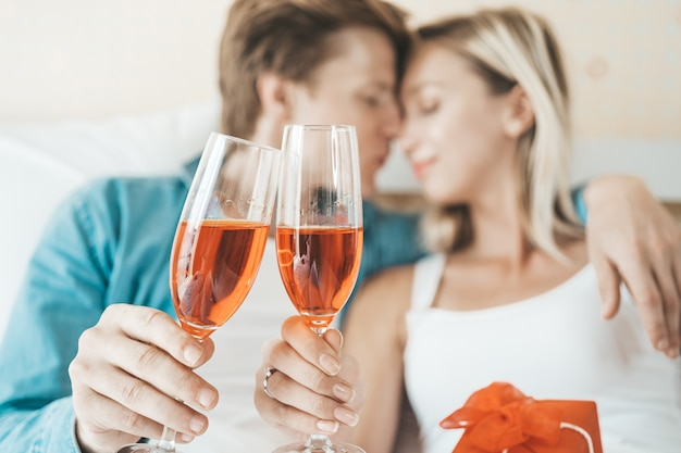 Coppie felici che bevono vino nella camera da letto Foto Gratuite