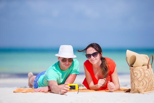 Coppie felici che prendono una foto di auto su una spiaggia in vacanza Foto Premium