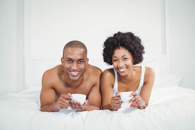 Coppie felici che si trovano sul letto mentre tenendo le tazze a casa Foto Premium