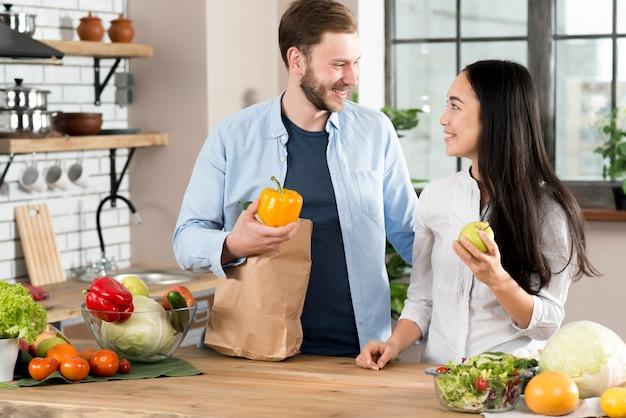 Coppie felici che stanno nella cucina che se lo esamina in cucina Foto Gratuite
