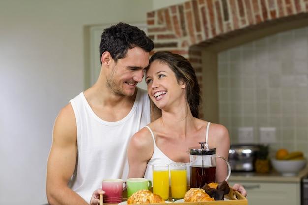 Coppie felici che tengono un vassoio di prima colazione in cucina Foto Premium