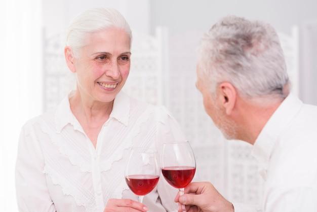 Coppie felici che tostano i bicchieri di vino insieme a casa Foto Gratuite