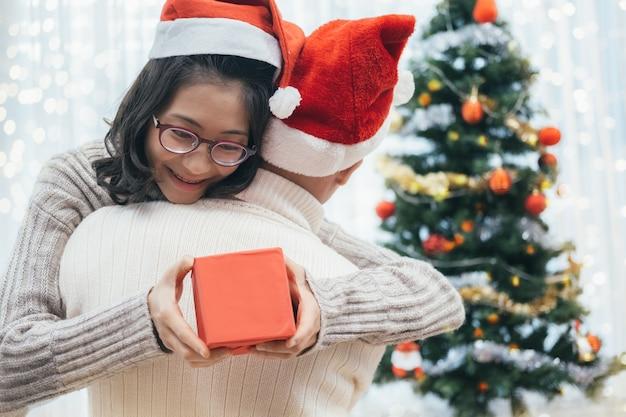 Coppie felici con seduta e abbracciare del regalo di natale. Foto Premium